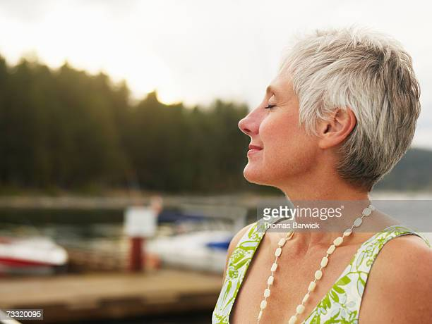 Senior woman outdoors, smiling, eyes closed, side view