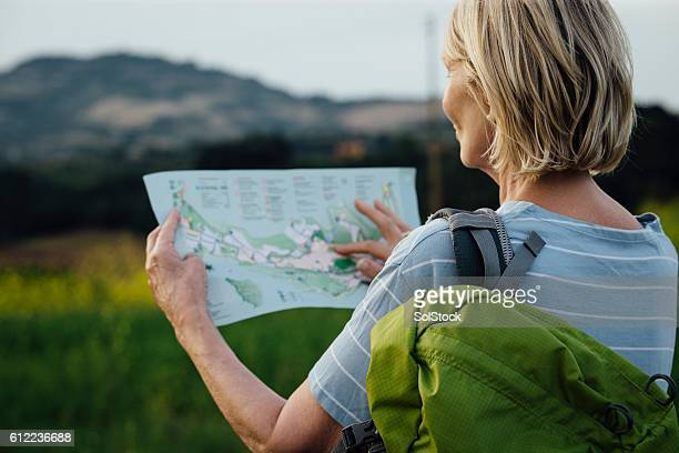 senior woman outdoors with a map and backpack - karte navigationsinstrument stock-fotos und bilder