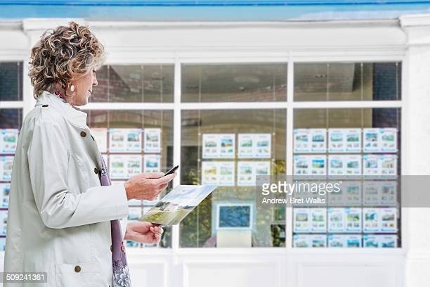 senior woman outside estate agency uses mobile - estate agency stock photos and pictures