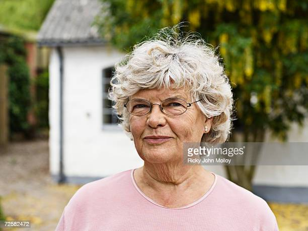 senior woman outside house with tree, portrait - frau 65 jahre stock-fotos und bilder