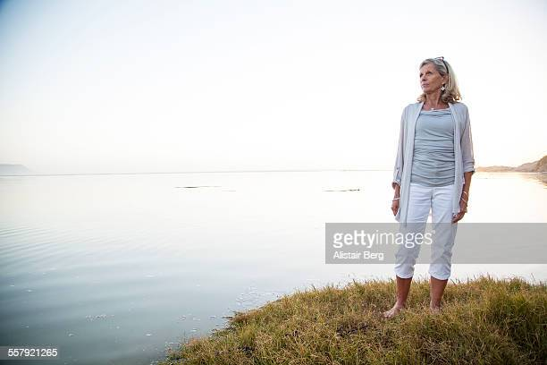 senior woman overlooking sea - white pants stock pictures, royalty-free photos & images