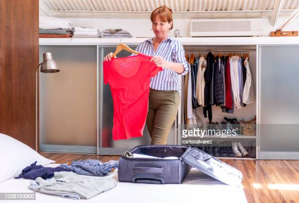 senior woman packing luggage - one senior woman only stock pictures, royalty-free photos & images