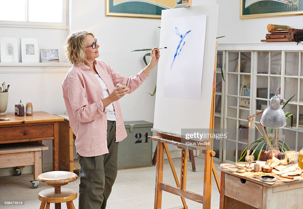 Senior woman painting at her home studio : Foto de stock
