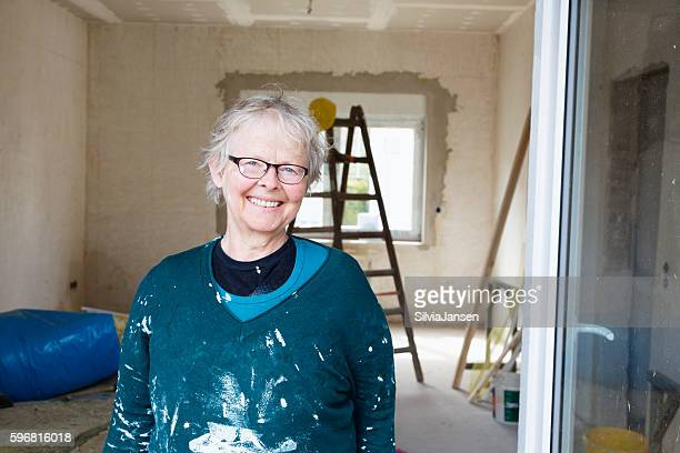senior woman painting her new house happiness