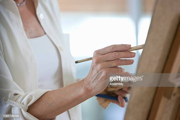 senior woman painting on easel