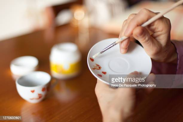 senior woman painting pottery - saucer stock pictures, royalty-free photos & images