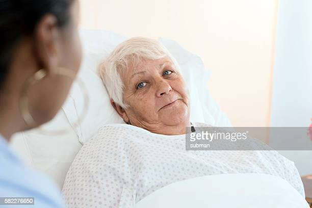 senior woman patient with female doctor - old woman in sick bed stock photos and pictures