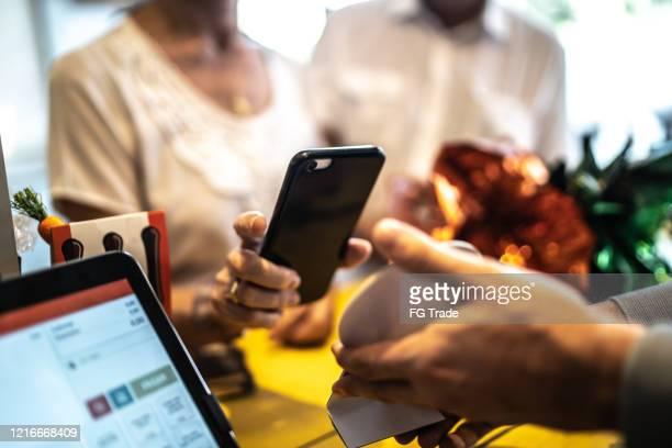 seniorin zahlt mit dem handy in einem geschäft - bezahlen stock-fotos und bilder