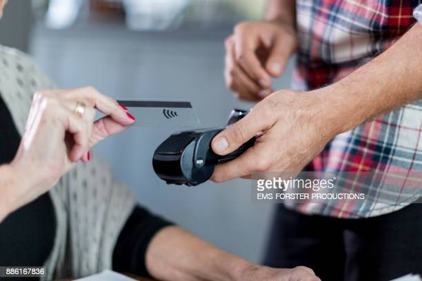 senior woman paying cashless with her credit card