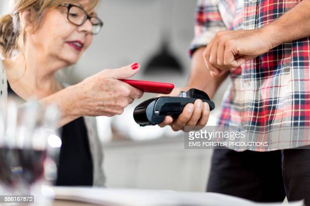senior woman paying with her mobile phone