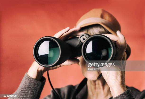senior woman peers curiously through binoculars, - curiosità foto e immagini stock