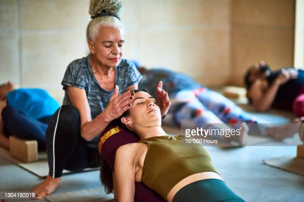 senior woman performing reiki o woman in yoga class - wellbeing stock pictures, royalty-free photos & images