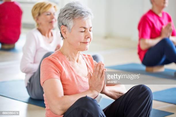 Haute femme effectuant l'yoga au club de santé
