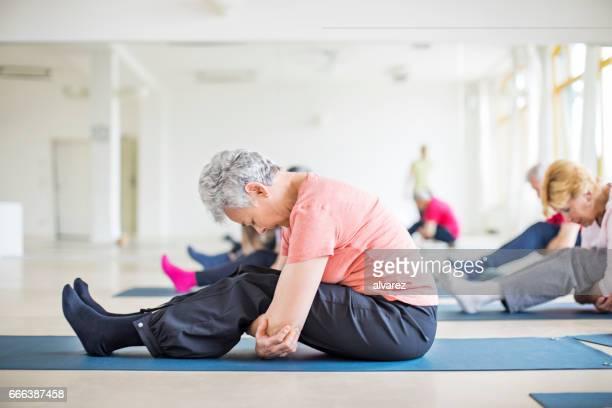 Ältere Frau, die Durchführung Yoga im Health club