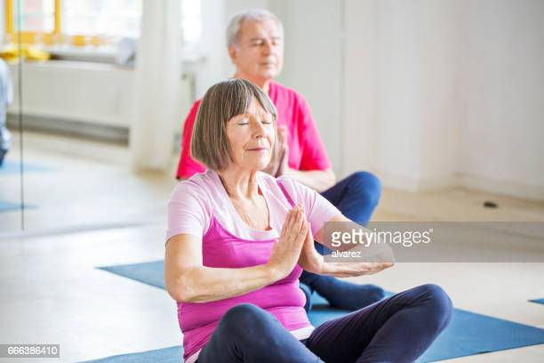 Senior woman performing yoga with friends in class