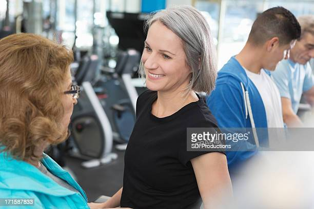 A senior woman personal trainer and gym clients workout.