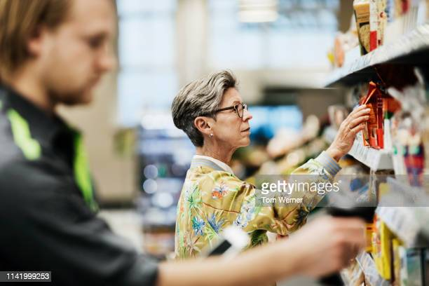 senior woman picking goods from shelf at supermarket - consumentisme stockfoto's en -beelden