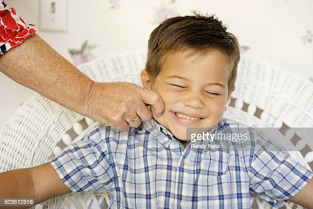 senior woman pinching boy's cheek - cheek stock pictures, royalty-free photos & images