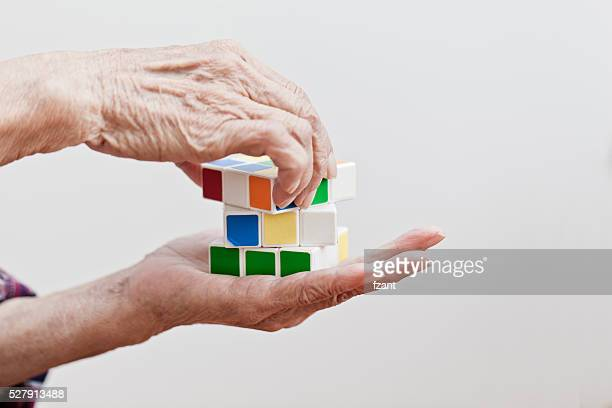 Senior woman playing a cube game