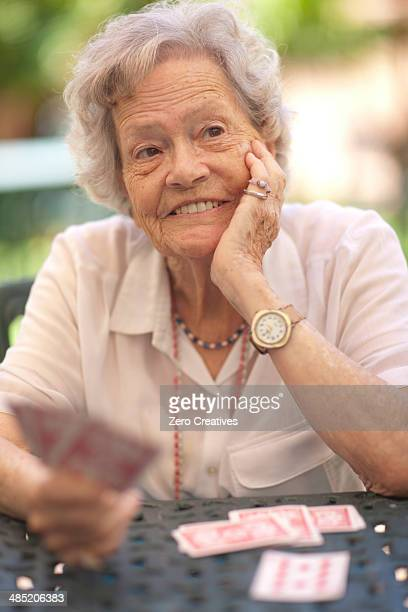 senior woman playing cards at garden table - thinking of you card stock pictures, royalty-free photos & images