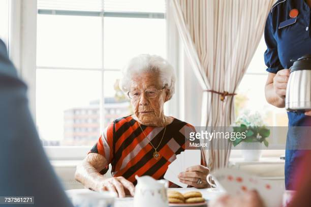 senior woman playing cards with family while caretaker holding coffee pot at home - mid section stock photos and pictures