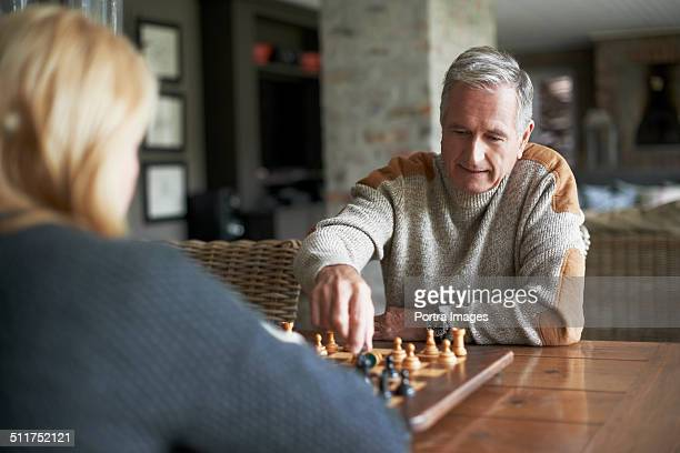 Senior woman playing chess with man