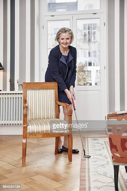 Senior woman playing golf at home
