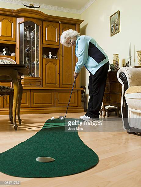 senior woman playing golf in living room