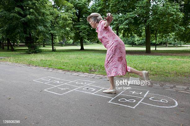 senior woman playing hopscotch - old lady funny stock pictures, royalty-free photos & images