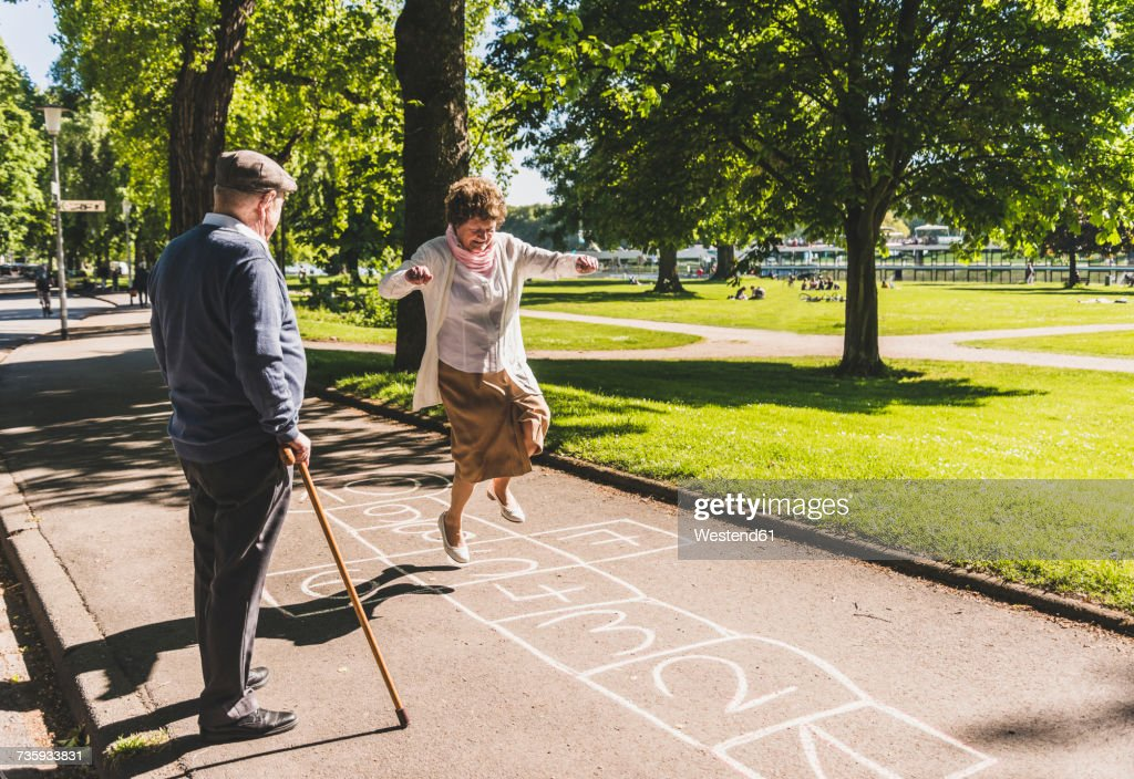 Senior woman playing hopscotch while husband watching her : Stock-Foto