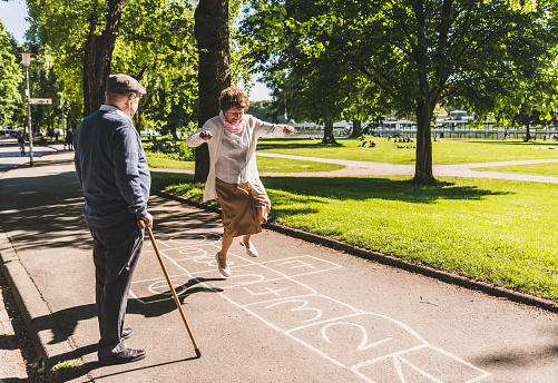Senior woman playing hopscotch while husband watching her - gettyimageskorea