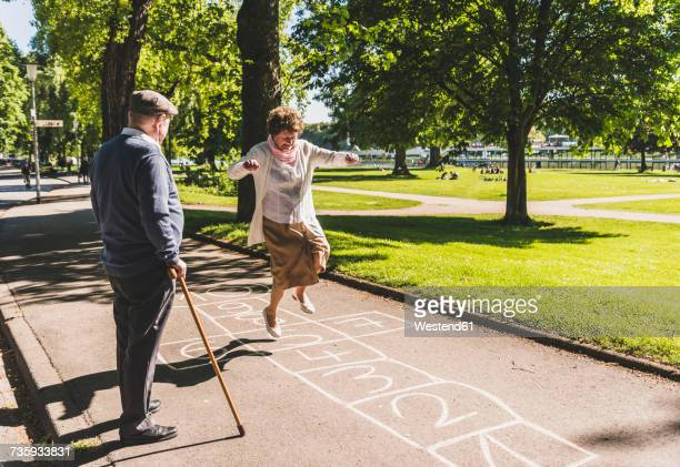senior woman playing hopscotch while husband watching her - spaß stock-fotos und bilder