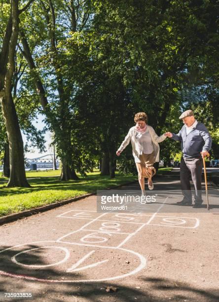 Senior woman playing hopscotch while husbanf watching her