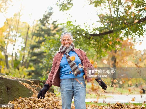 senior woman playing in autumn leaves. - roupa quente - fotografias e filmes do acervo