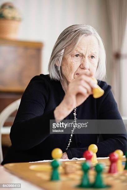 Senior woman playing Ludo at nursing home