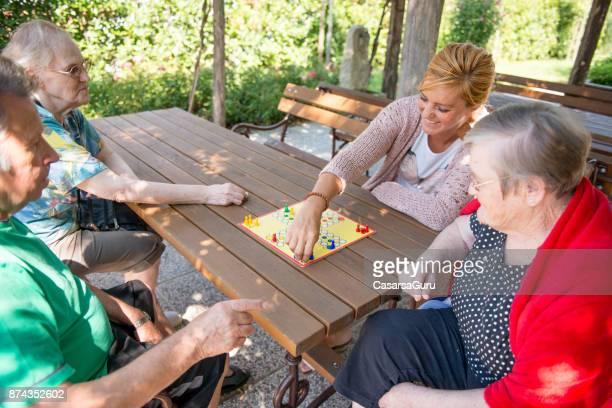 Ältere Frau spielt Ludo Brettspiel mit Frau Hausmeister