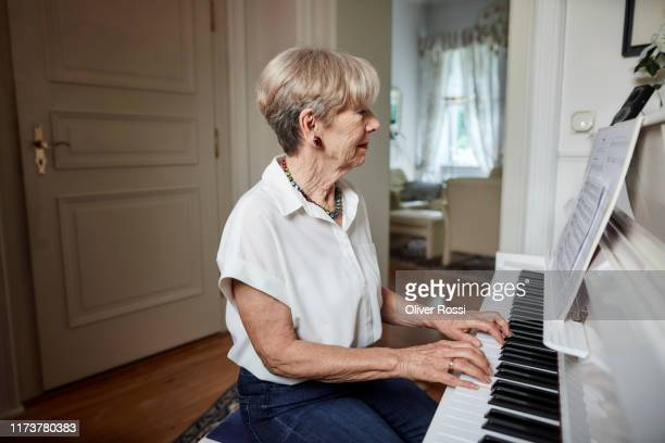 senior woman playing piano at home - piano stock pictures, royalty-free photos & images