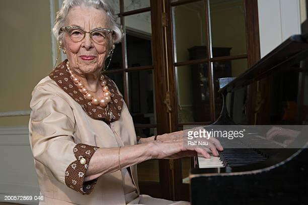 senior woman playing piano, smiling, portrait - solo una donna anziana foto e immagini stock