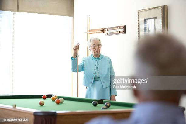 senior woman playing pool, indoors - old men playing pool stock pictures, royalty-free photos & images