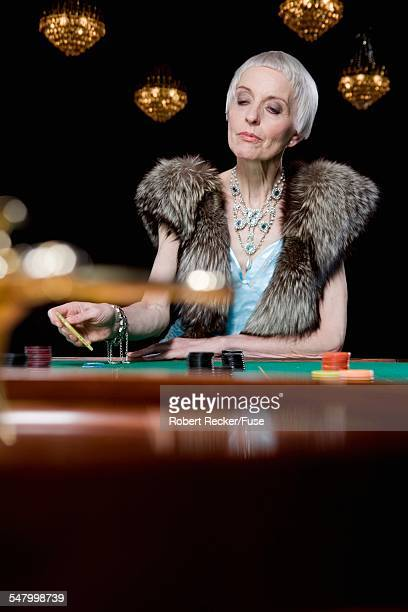 senior woman playing roulette - gambling table stock pictures, royalty-free photos & images