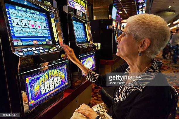 Senior woman playing slot machines