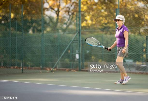 senior woman playing tennis - tennis player stock pictures, royalty-free photos & images