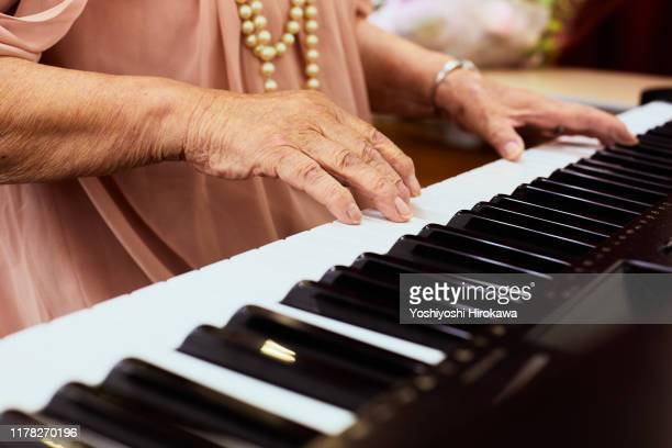 senior woman playing the piano - keyboard player stock pictures, royalty-free photos & images