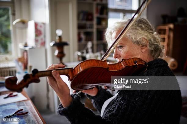 Senior woman playing violin at home