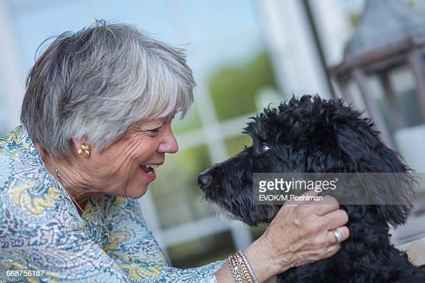 Senior woman playing with dog