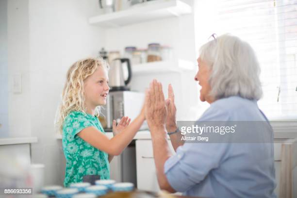 senior woman playing with her grand daughter at home - granddaughter stock photos and pictures