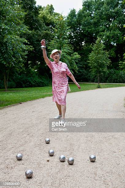 Senior woman plays Boules in the park