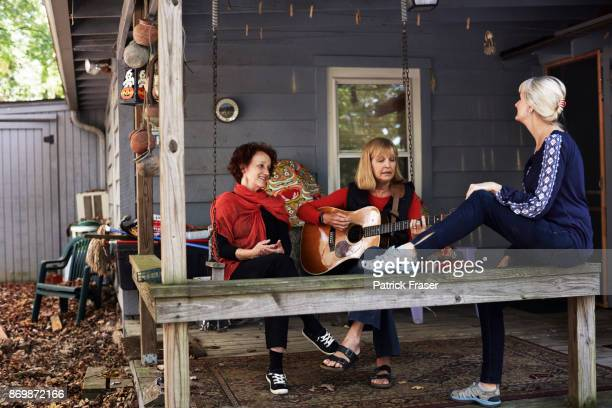 Senior woman plays guitar for two other senior women on porch