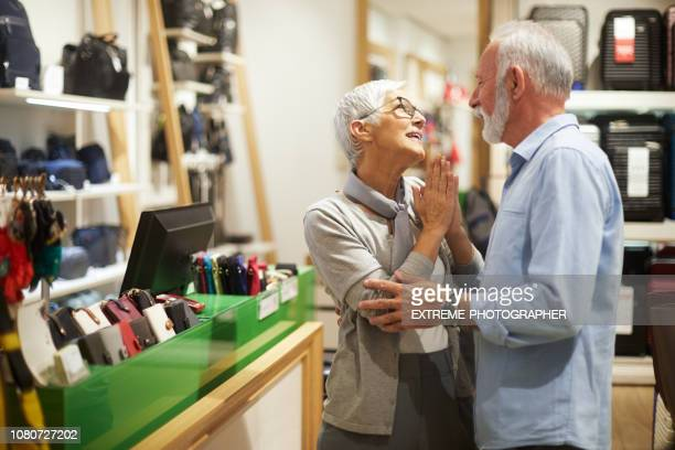 Senior woman pleading her partner for something from the bags and accessories store while he is refusing