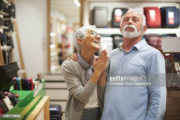 Senior woman pleading her partner to buy her something from the bags and accessories store while he is refusing